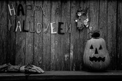 Black and white Halloween background. Black and white Jack pumpkin head with spider, witch, severed hand and an inscription on a wooden background Happy Royalty Free Stock Image