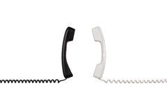 Black and white handsets are arranged vertically towards each other Royalty Free Stock Photography