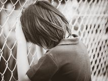 Black and white of handsome sad boy holding fence mesh netting. Emotions concept. Sadness, sorrow, melancholy. Fashion & beauty concept royalty free stock images