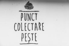 Black and white handwritten grocery sign in romanian. Horizontal. Black and white picture of a handwritten grocery sign, on a white wall of a romanian store Stock Photo