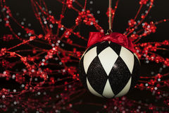 Black White Harlequin Christmas Ornament. A hanging harlequin patterned ornament in black and white with red bow, red and white sparkling bokeh on black Royalty Free Stock Photos