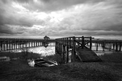 Black and white high contast lake with wooden bridge and boat in Stock Photography