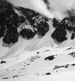 Black and white high mountains with snow cornice and avalanche tracks. High mountains with snow cornice and avalanche tracks, snowy plateau and small silhouette stock photos