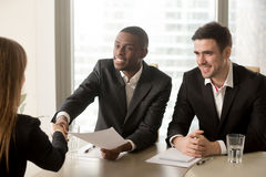 Black and white hr recruiters welcoming applicant on job intervi. Two cheerful black and white recruiters welcoming female applicant on job interview, african Stock Images