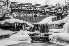 Black white icy waterfall under bridge Stock Photos