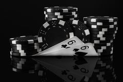 Black white idea of poker chips and poker cards in poker on a black stock photography