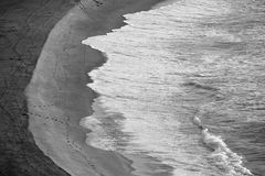 Black and white image 4. Another black and white images taken from a cliff looking down on the sand, ocean and the footsteps of the early morning walkers Royalty Free Stock Image