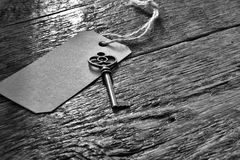 Antique Key and Gift Tag. A black and white image of an antique house key with paper note tag Stock Photos