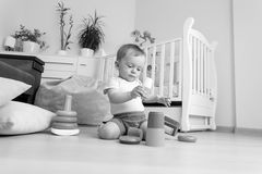 Black and white image of baby boy playing on floor with blocks a Royalty Free Stock Image