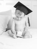 Black and white image baby in graduation hat using tablet Royalty Free Stock Images