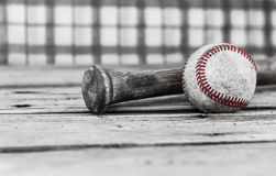 Black and white image of a baseball and bat on wood surface.