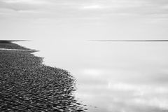 Black and white image of beach at low tide landscape Stock Images