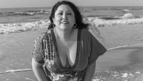 Black and white image of a beautiful latin woman wearing casual clothes enjoying a wonderful day on the beach royalty free stock image