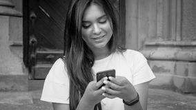 Black and white portrait of beautiful smiling woman using mobile phone on street stock image