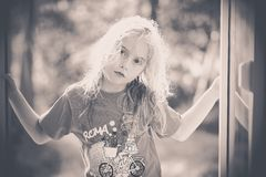 Black and white image of a blond little girl looking at me stock image