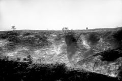 Couple Walks on Ridge Line with Burned Landscape Below in Black and White royalty free stock photography