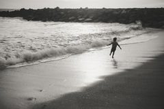 Black and white image of child running on evening Stock Photos