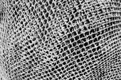 Macro Closeup of Hand knotted Fishing Net. A black and white image of the closeup diamond pattern and texture of a large folded fishing net royalty free stock photography