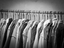 Black and white image of clothes hanging on hanger rack. Choice of fashion clothes on hangers Stock Photos