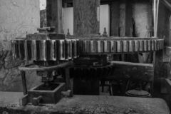 A black and white image of the cogs inside a watermill in Devon, England, taken from the right of the cogs stock image