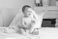 Black and white photo of cute smiling baby boy with bottle of milk sitting on bed. Black and white image of cute smiling baby boy with bottle of milk sitting on Stock Image