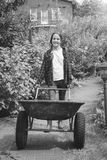 Black and white image of cute young teen girl posing with wheelbarrow at garden stock photos