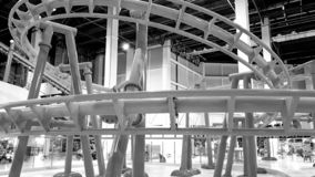 Black and white image of extreme roller coaster with loops in amusement park. Black and white photo of extreme roller coaster with loops in amusement park stock images
