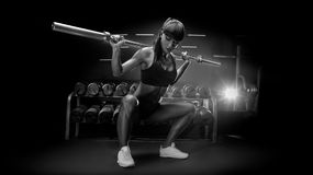 Black and white image of fit young woman in great shape lifting. Barbells looking down, working out in a gym Sporty woman doing squat workout Strong legs stock photos