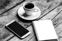 Black and white image of freelancer workspace. Mobile phone, notebook and cup of strong coffee on wooden table Royalty Free Stock Photos