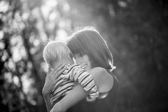 Black and white image of a happy smiling young mother hugging he Royalty Free Stock Photos