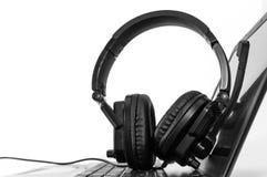 Black and white image, headphone on laptop computer. White background stock photo