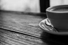Black and white image of hot coffee cup on vintage wooden table. In cafe royalty free stock photography