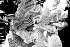Decorative three headed white dragon. A black and white image of an incredibly intricate statue sculpture of a 3 headed dragon guarding an ancient buddhist stupa Stock Photo