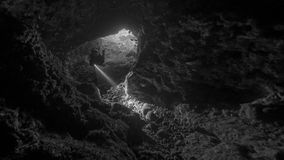 Cave diving in Alor. Black and white image from the inside of an undersea cave as a diver swims towards the photographer holding a torch. Spot the giant moray Stock Photo