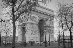 Black and white image of l`arc de triomphe in Paris. France with busy city street of cars and people Royalty Free Stock Images