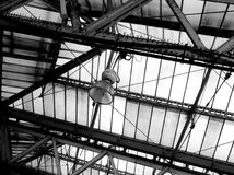 Black and White Image of Lamp Suspended from Glass Roof. Lamp suspended from truss beneath glass roof in black and white Stock Photos