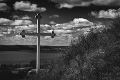 Black and white image of a large  cross sitting on side of hill. Stock Photo