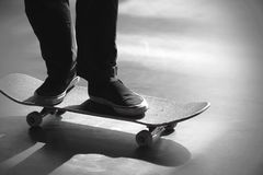 Black and white image of the legs of a man  riding on his skateboard royalty free stock images