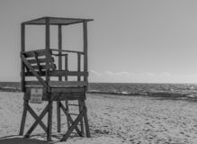 Waiting for the crowds. Black and White image of a lone lifeguard chair standing vacant on an empty beach on Cape Cod. Small ocean waves rolling in under a vast royalty free stock photography