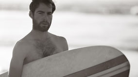 Black and white image of male surfer and retro surfboard. Black and white image of young male surfer holding a surfboard under his arm while looking into the Stock Photo