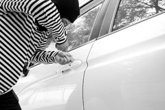 Black and white image of the man robber with a balaclava on his head trying to break into the car/Criminal and car. Black and white image of the man robber with Stock Images