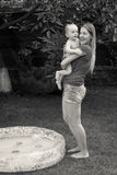 Black and white image of mother hugging her baby boy after swimming in outdoor swimming pool. Black and white image of young mother hugging her baby boy after stock photography