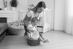 Black and white image of mother sitting her baby on chamber pot stock photos
