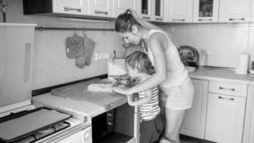 Black and white image of young mother teaching her 3 years old toddler son cooking and baking cookies on kitchen. Black and white image of mother teaching her 3 stock image