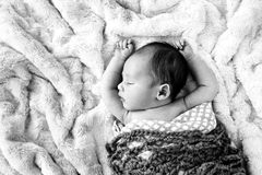 Black and white image of New Baby sleeping. Wrapped in crotchet wool blanket on fur rug with arms out - caucasian and pacific islander ethnicity Stock Images