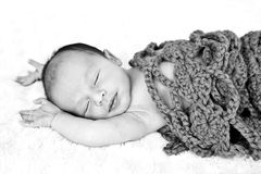 New Baby sleeping wrapped in crotchet wool blanket. Black and white image of New Baby sleeping wrapped in crotchet wool blanket on fur rug with arms out Stock Photo