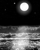 Full Moon Over the Ocean Waves with Stars at Night. Black and white image of the Ocean waves crashing over as the stars shine and the full moon glows in the Royalty Free Stock Image