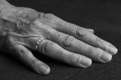 An old hand with a ring on one finger. Black and white image of an old hand with a ring on one finger Stock Photo