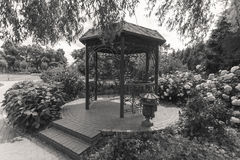 Black and white image of old metal alcove under tree at park Stock Image