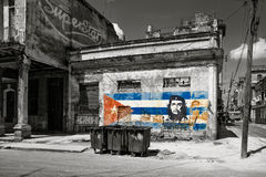 Black and white image of old shabby buildings in Havana with a painting of Che Guevara and a cuban flag Stock Image